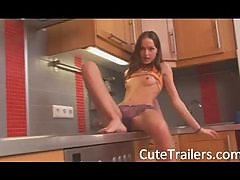 Thin girl teasing body on a kitchen unit