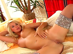 Busty babe in stockings fingers her shaved pussy. Big boobed blonde ..